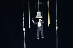 Hanging man ringing the bell for new year�s first performance Royalty Free Stock Images