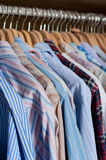 Hanging men's shirts. This is an image of ironed and pressed shirts neatly hanging inside a wardrobe on wooden hangers stock images