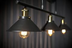 Hanging metal construction with retro light bulbs. With black background royalty free stock images