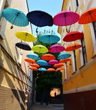 Hanging Multicoloured umbrellas over blue sky Stock Images