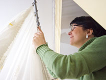 Hanging net curtains. A woman hanging new net curtains at a window Royalty Free Stock Photo