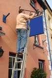 Hanging a New Sign. Middle aged man up a ladder hanging a new blue sign from a cast iron ornate bracket (blank) on the side of a building stock image
