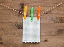 Hanging notebook  with colored clothespins on  wood background Royalty Free Stock Image