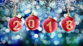 Hanging 2018 number glitter Christmas balls on blue bokeh background. Stock Image