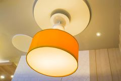 Hanging orange glow creative design lamp on restaurant ceiling for decoration. Close up hanging orange glow creative design lamp on restaurant ceiling for Royalty Free Stock Image
