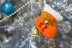 Hanging orange handicraft Xmas stocking and golden bell Royalty Free Stock Photos