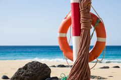 Orange life belt at the beach. Hanging orange life belt with long rope at the beach, security and safety concept stock photos