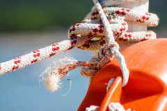 Hanging orange life belt with long rope at the beach, security and safety concept.  royalty free stock photos