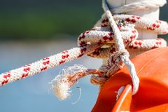 Hanging orange life belt with long rope at the beach, security and safety concept.  stock photos
