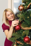 Hanging ornaments on a Christmas tree. Photo of a beautiful blond female hanging ornaments on a Christmas tree Royalty Free Stock Photo