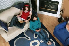 Hanging out. Two teen-aged girls hang out in the living room, sitting comfortably as they look in front of them, possibly at the television set Royalty Free Stock Images