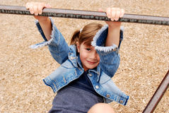 Hanging out. A cute young girl playing on the monkey bars Royalty Free Stock Photography