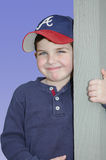 Hanging Out. Little boy with big beatiful blue eyes, stands next to a pillar and gives a cute grin Royalty Free Stock Images