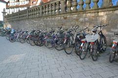 Hanging out on a bicycle parking lot. Filled parking for bicycles. Bicycles lined up like they have no end. Parking exudes energy and health. Wall with a nice Stock Photos