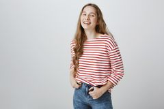 Hanging out and communicating with friends. Portrait of attractive young european girl in trendy outfit posing over gray. Wall and smiling broadly at camera Stock Images