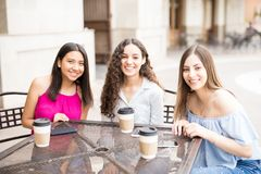 Hanging out at outdoor coffee shop. Portrait of beautiful young girl friends sitting at a cafe having coffee Stock Photos