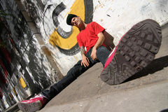 Hanging out. A Rapper leaning against a Graffiti wall Royalty Free Stock Photo