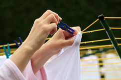 Hanging out the washing. Hands pegging out the washing on the line of a rotary clothes dryer royalty free stock photos