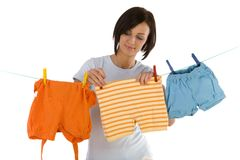 Hanging out washing. Young smiling woman hanging clothes on clothesline using clothespin. Front view, white background royalty free stock photo