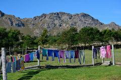 Hanging out the washing. Clothes drying in the sun on a farm fence Stock Photo