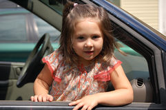 Hanging out of the window. Four year old girl leaning out of the window of a car Stock Photos
