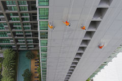 Hanging painters is painting high building. Hanging painters is painting high condominium building Stock Image