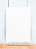 Hanging paper poster frame at ceramic tiles wall and wooden plan Royalty Free Stock Photo