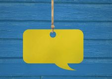 Hanging paper speech bubble and wood background. Digital composite of Hanging paper speech bubble and wood background Royalty Free Stock Image