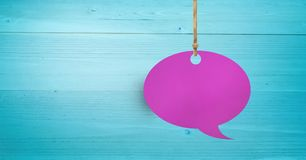 Hanging paper speech bubble and wood background. Digital composite of Hanging paper speech bubble and wood background Stock Images