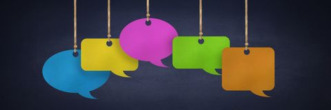 Hanging paper speech bubbles and blackboard background. Digital composite of Hanging paper speech bubbles and blackboard background Stock Photo