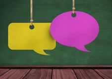 Hanging paper speech bubbles and blackboard background. Digital composite of Hanging paper speech bubbles and blackboard background Royalty Free Stock Photography