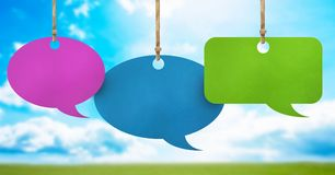 Hanging paper speech bubbles and sky background. Digital composite of Hanging paper speech bubbles and sky background Stock Images