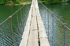 Hanging pedestrian bridge across the river Royalty Free Stock Images