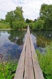 Hanging pedestrian bridge across the river Stock Image
