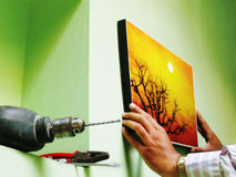 Hanging a picture on wall. A man hanging a picture on the wall, the tools are at hand Royalty Free Stock Photo