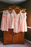 Hanging Pink Bridesmaid Dresses. Four blush pink chiffon bridesmaids dresses hanging on a wooden wardrobe closet on the morning of a wedding Stock Photos