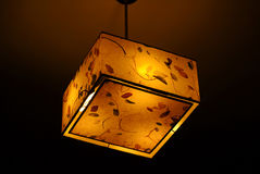 Hanging plastic square ceiling lamp with a yellow dim light Royalty Free Stock Photo