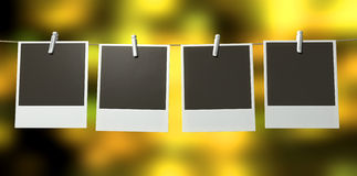 Hanging Polaroid Gallery. A gallery of four blank polaroids pegged onto a string on a blurry abstract yellow background royalty free stock image