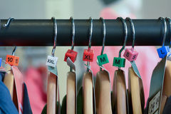 Hanging rail with clothes and sizes on rail Royalty Free Stock Photography
