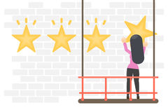 Hanging rating stars. Woman hang golden star on the wall Stock Images