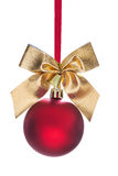 Hanging red christmas bauble with gold colored bow and small bel Royalty Free Stock Image