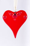 Hanging Red Glass Heart. A red glass heart suspended from a cream ribbon set against a white background Stock Images