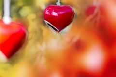 Hanging red heart ceramic mobile valentine`s day background. Hanging red heart ceramic mobile and blurry background for valentine`s day February romantic royalty free stock photo