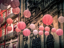 Hanging red lanterns on historic street in Porto. Red and pink lantern hang on a street in historic portugal Royalty Free Stock Photos