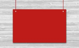 Hanging red sign on wooden background. Royalty Free Stock Photos