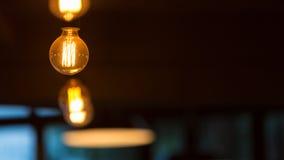 Hanging retro light bulbs. Against dark background Stock Photo