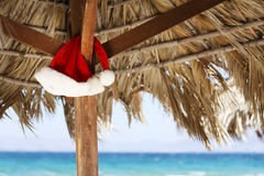 Hanging Santa Claus hat on palmy sunshade Stock Photo