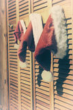 Hanging Santa Hats. Two adult and one small sized santa hats hanging from a closet door royalty free stock photos