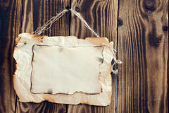 Hanging scorched paper on a wooden background. Scorched paper hanging on a rope on a wooden brown background Royalty Free Stock Photos
