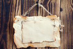 Hanging scorched paper on a wooden background. Scorched paper hanging on a rope on a wooden brown background Stock Image